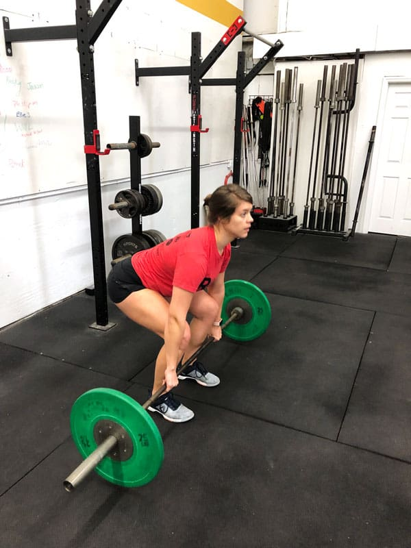 woman in gym with barbell in clean setup position