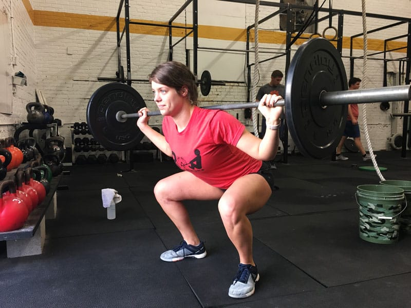 woman in gym with barbell on shoulders