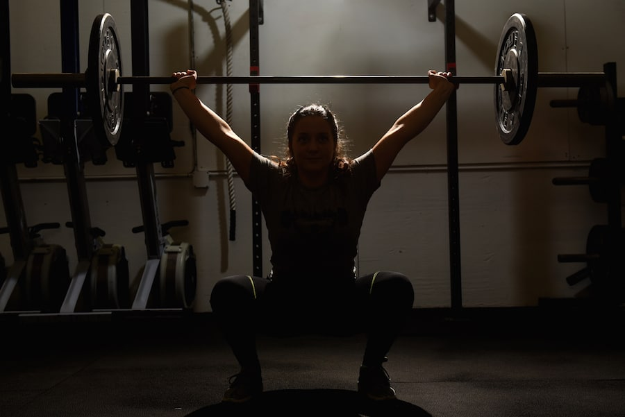 image of woman squatting with a barbell overhead
