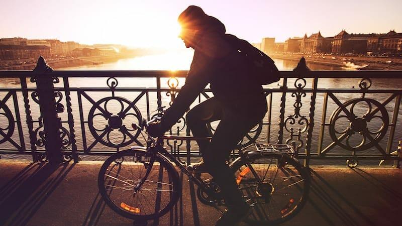 man riding a bike across bridge at sunset