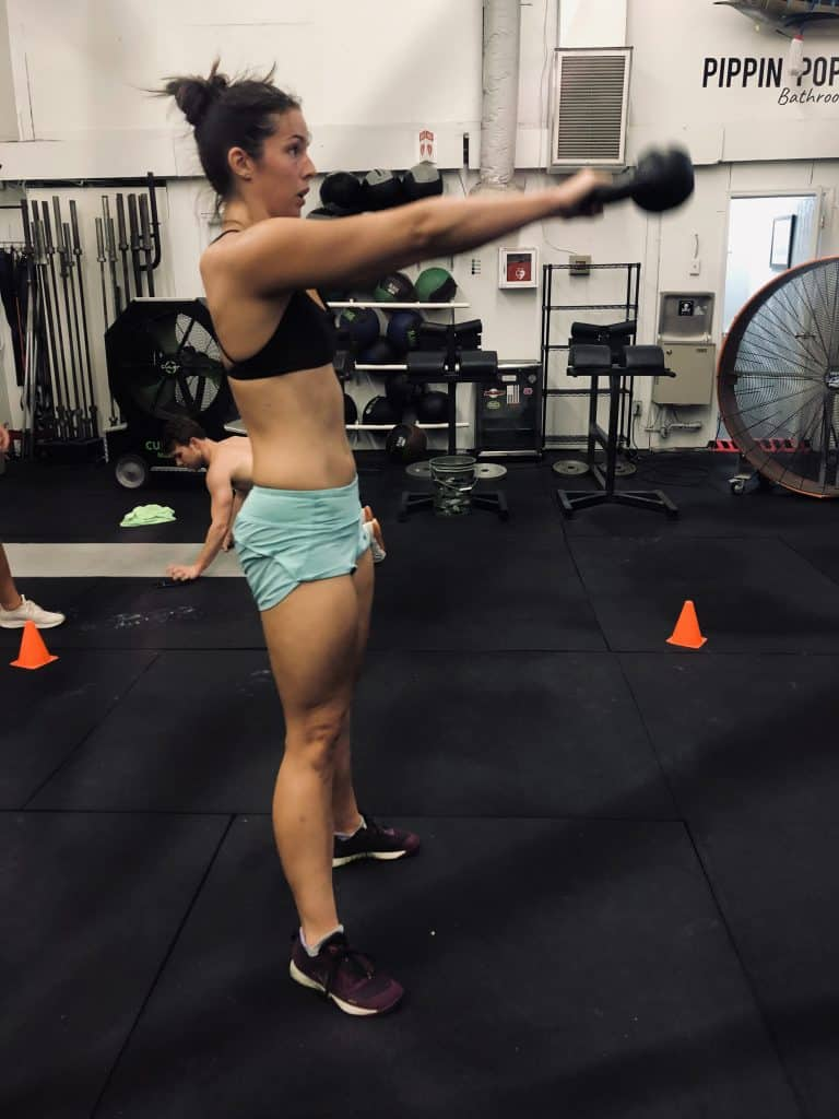 Woman in gym doing a russian kettlebell swing